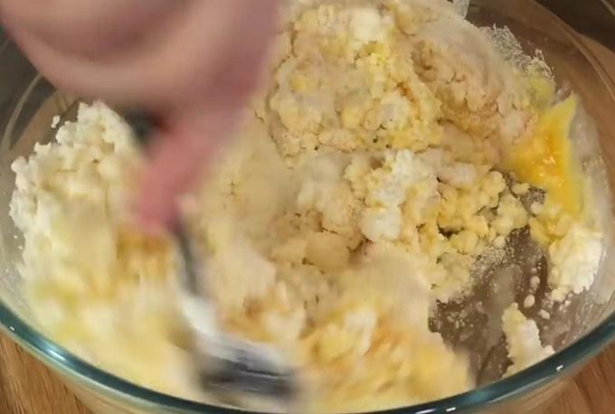 Перемешиваем творог с яичными желтками и манкой